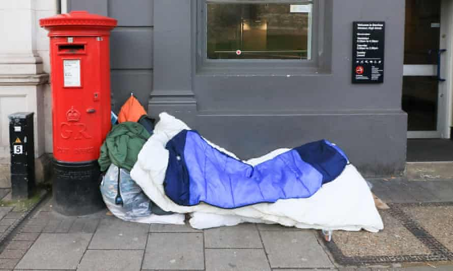 Homeless person sleeping on pavement