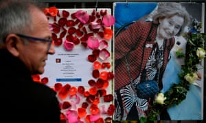 A man stands in front of a picture of Mireille Knoll placed on the fence surrounding her building in Paris.