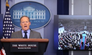 Sean Spicer delivers a statement on 21 January 2017 while a television screen shows a picture of Trump's inauguration.