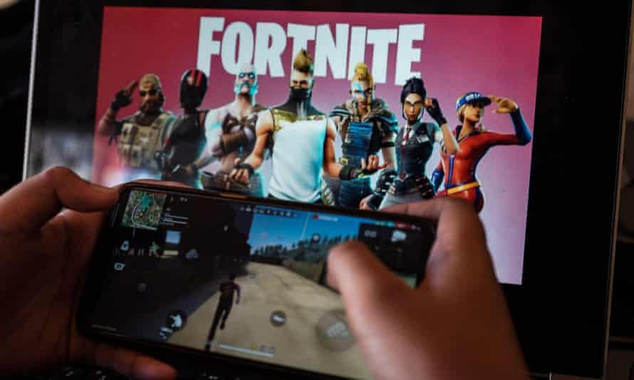 Picture of a child playing Fortnite on a phone, with a title screen for the game on a larger screen int he background.