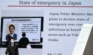A man walks past a screen showing the news that Japanese prime minister Shinzo Abe plans to declare a state of emergency over the coronavirus outbreak.