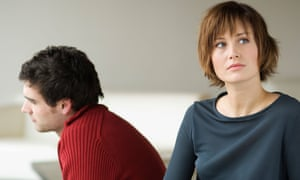 Troubled looking couple facing away from each other in a living-room