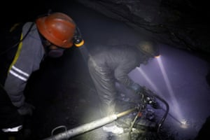 Miners use a drilling machine to search for gold in a mine