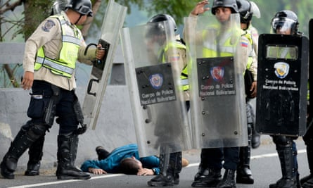 An injured man lies next to national guard members during a demonstration in Caracas, Venezuela on 11 May, 2016. A 60-day state of emergency has been declared.
