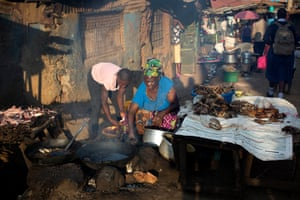 Women cook fish in the evening light to sell to passers by in one of the main streets of Kibera. Some of the sellers cannot afford to eat the stock they are selling to others