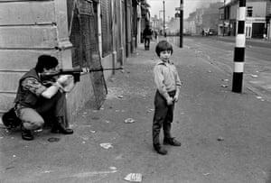 Soldier pointing rifle, bottom of Clonard Street, Belfast, 1978