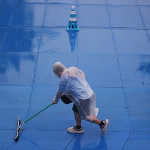 A worker during rainy weather prepares the track for the women's triathlon at the Tokyo Olympics.
