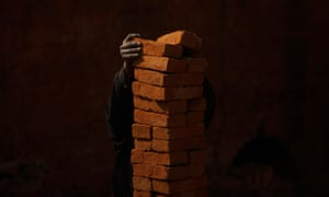 A worker stacks bricks on his head at a brick factory in Nepal