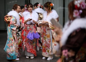 Women wearing kimonos share a joke as a friend looks on.