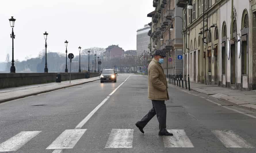 A lone pedestrian crosses the road in Turin