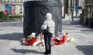 A member of the public looks at floral tributes left at a Hillsborough memorial in Old Haymarket, Liverpool.