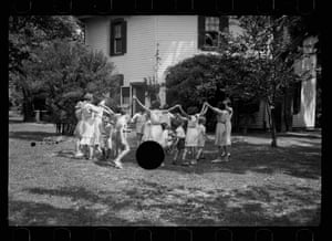 children playing with large black circle in centre of picture