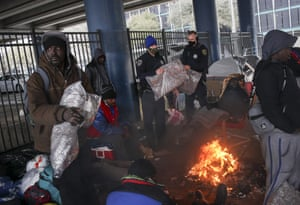 Houston Police officers Kenneth Bigger, center, and Aaron Day, center right, hand out blankets to people under the elevated portion of I-45 in downtown Houston, Tuesday, Feb. 16, 2021,