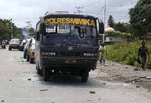 People walks past a police bus damaged during a protest in Timika, West Papua Province,Wednesday, Aug. 21, 2019.