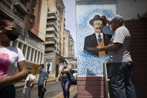 Artist Mervin Marmol puts the finishing touches to his painting at the street corner where Hernandez died in a car accident in 1919, in La Pastora neighborhood in Caracas