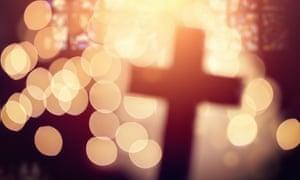 Defocussed cross silhouetted in church interior.