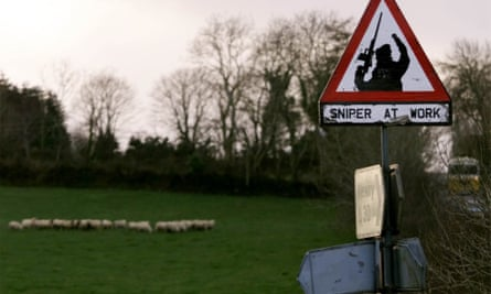 Sheep graze next to a 'sniper at work' sign in rural South Armagh in 1999.