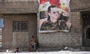 A Syrian soldier sits below a poster on Bashar al-Assad