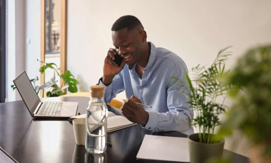 Smiling businessman in blue shirt talking on cell phone and arranging meeting, looking down in his planner while sitting at black desk in his office.