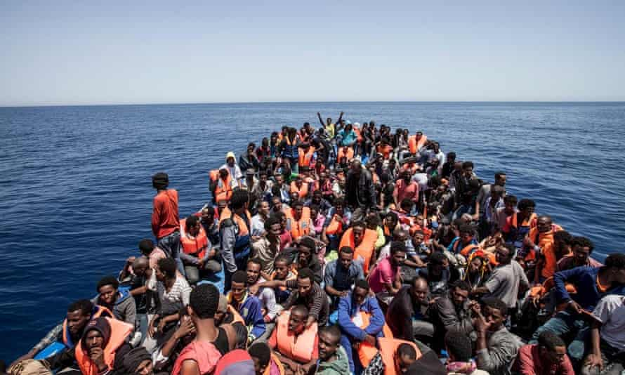 Migrants crowd the deck of their wooden boat off the coast of Libya.