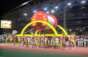 A team of surf lifesavers carry an oversized spool of rope during the Olympics closing ceremony.