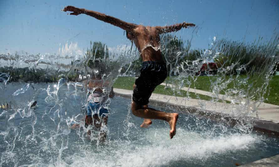 People play in a waterfall at Yards Park in Washington DC. Temperatures in the capital were set to reach 100F this weekend.