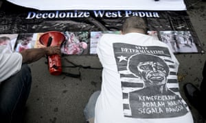 An Indonesian activist kneels before West Papuan pro-independence demonstrators.