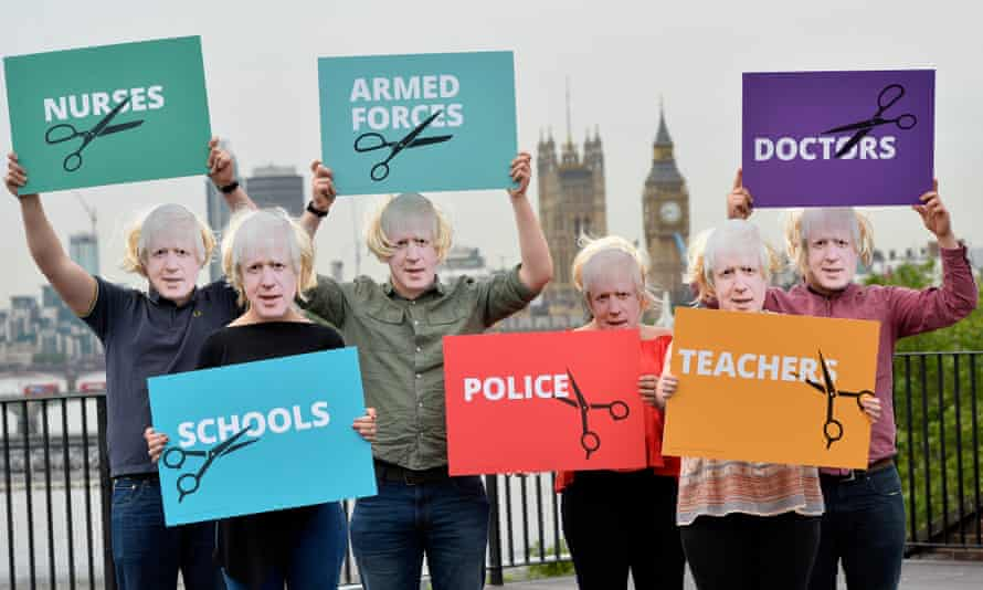 People dressed as Boris Johnson hold placards showing the groups of people that will be affected most by a Tory Brexit.
