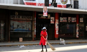 A woman sweeps the street outside the opposition headquarters in Harare.
