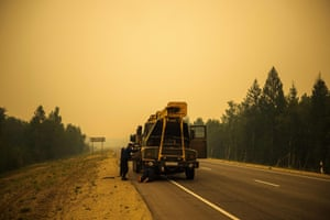 Men repair their truck in smoke from a forest fire on a road near Magaras