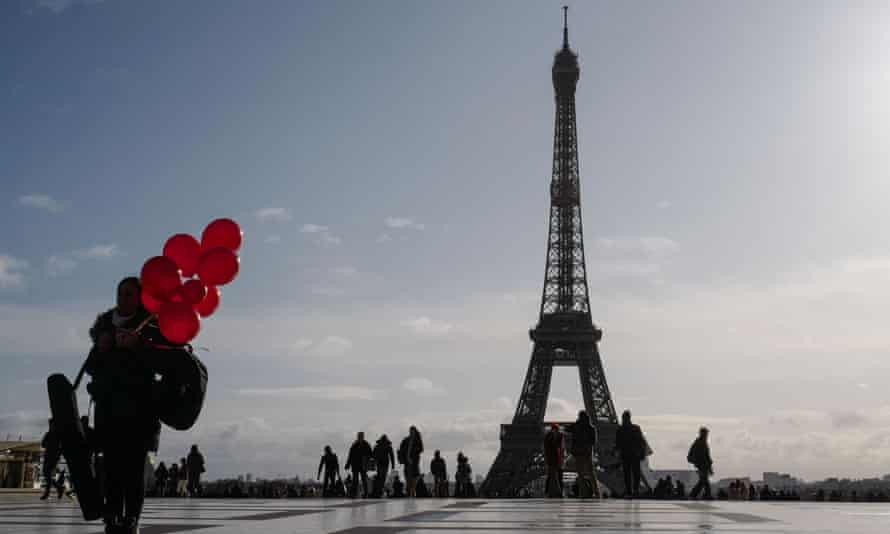 A woman holds red balloons on the Trocadero Plaza, in front of the Tour Eiffel