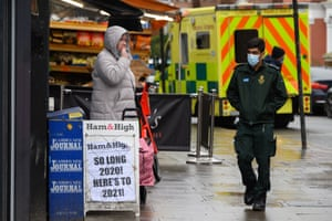 A paramedic walks past a newspaper hoarding celebrating the arrival of the new year, outside a newsagent near to the Royal Free hospital