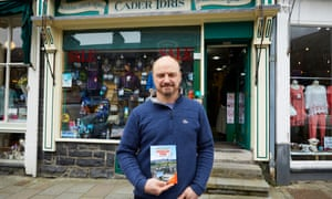 Cader Idris outdoor shop owner Andrew Ennever with the walking book purchased by Theresa May.
