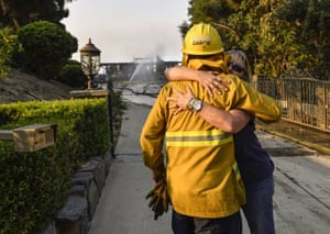 Vicky Walker hugs firefighter Jose Garcia as she thanks him for helping to save her home in Anaheim