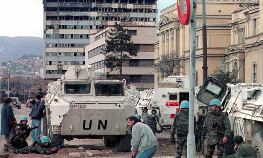 UN peacekeepers and Sarajevo citizens take cover from gunfire on the city's infamous 'Sniper Alley', March 1993.