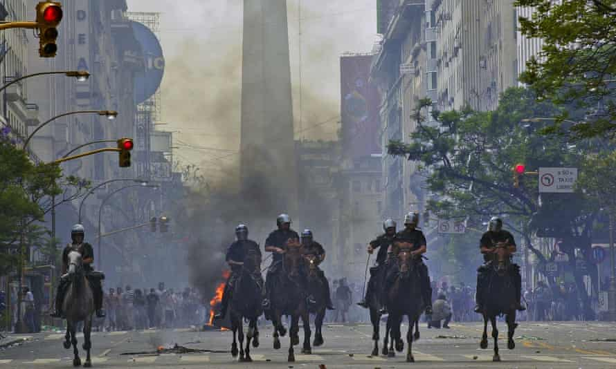 Police charge anti-government protesters in Buenos Aires after Argentina defaulted on $100bn in foreign debt in 2001. Annual per capita income fell from $8,500 to $2,800 in 2002.