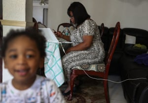 Jessie Morancy uses her computer to fill out the application for unemployment benefits as she stays home with her nephew, Freddy Preseler, after being laid off from her job at the Fort Lauderdale–Hollywood International Airport on 27 March 27 in Hollywood, Florida.