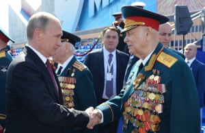 President Vladimir Putin shakes hands with a veteran in Moscow