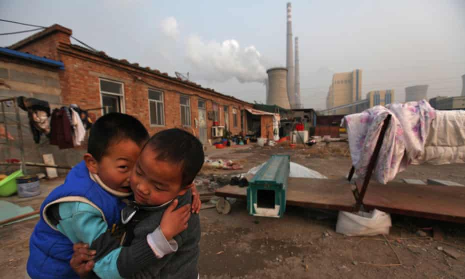 Chinese boys play in the courtyard of their home beside a power plant  in Beijing, China, 28 November 2011. Reports state that China, the world's largest emitter of greenhouse gases, is rallying key allies to push developed nations to agree to binding targets for reducing carbon emissions ahead of climate change talks in Durban even as it maintains that developing countries continue to be exempt as these would hamper efforts to alleviate poverty