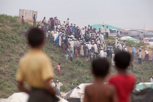 Boys watch a funeral on a hillside in Kutupalong camp