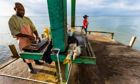 A man cleans fish while waiting for catch to arrive on dock.