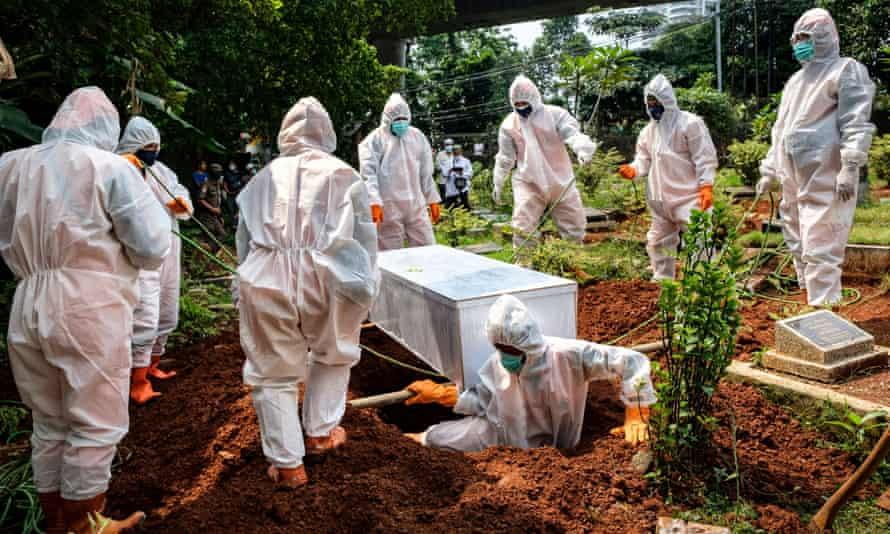 Petugas kesehatan pemerintah bertopeng menguburkan terduga korban Covid19 di Jakarta, Indonesia