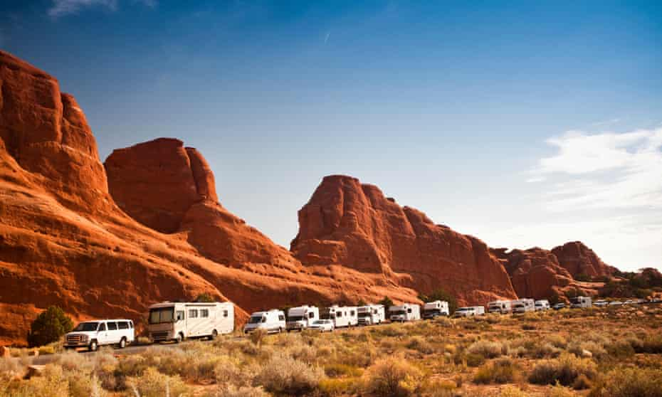 a queue of recreational vehicles and campervans at Arches national park near Moab, Utah.