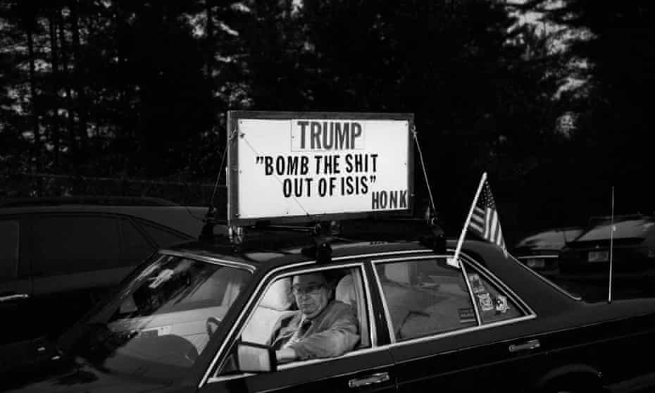 A man sits in a car with a sign on top outside a political event where Republican Presidential candidate Donald Trump is due to speak.