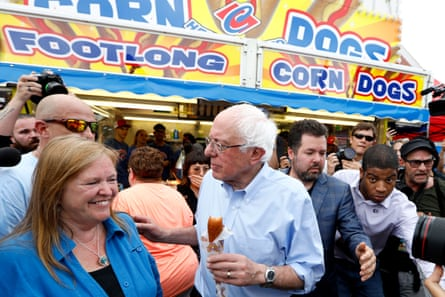 Democratic presidential candidate Sen. Bernie Sanders eats a corn dog with his wife Jane, left, during a visit to the Iowa State Fair.
