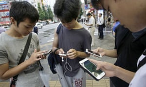 People gaze at their smartphones as they play Pokémon Go at Akihabara district in Tokyo.