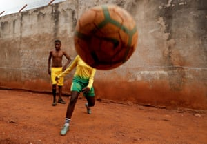 Gaelle Dule Asheri, 17, who is amongst the first wave of girls being trained by professional football coaches at the Rails Foot Academy, plays football with her friends outside her house in Yaounde, Cameroon