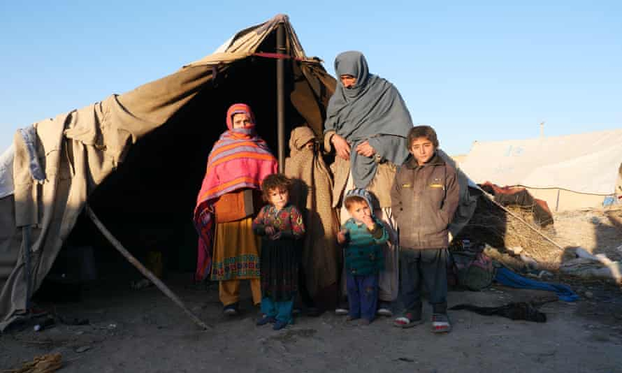 Qayoom and his children outside the tent they now call home. Their village was captured by the Taliban.