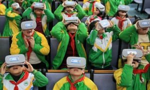 Chinese primary school pupils wear virtual reality headsets inside a classroom in Xiangxi.