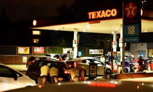 People pushing like a car, which has run out of gas, at a Texaco service station in South London, on September 26, 2021.